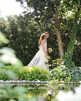 Bride and groom strolling through the Casanova gardens of Hotel Cipriani