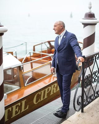 Doorman in a blue suit by a pier outside Belmond Hotel Cipriani