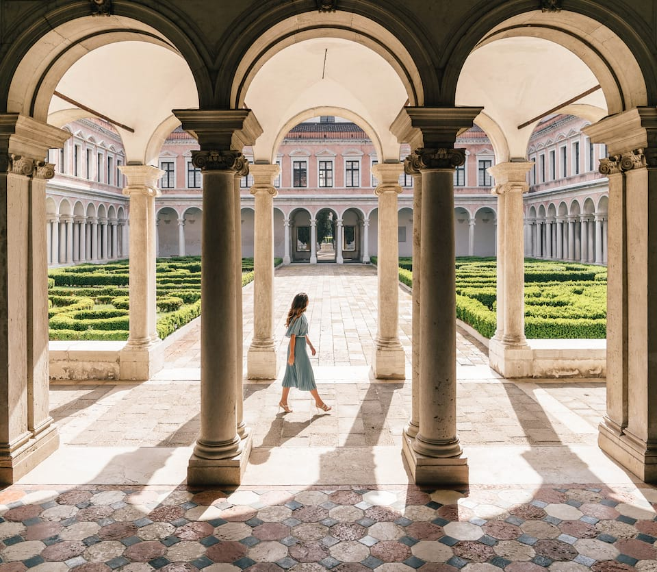 A lady walking though a courtyard of a historical venetian building
