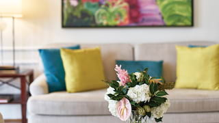 Pink and white flowers in a glass vase on a coffee table in front of a grey sofa
