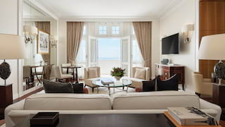 Glamorous hotel suite with white and beige accents and balcony with sea views