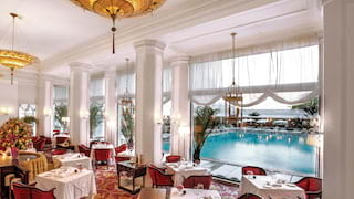 Formal restaurant with art deco chandeliers, tall ceilings and columned entrance