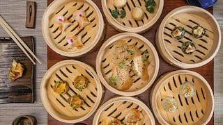 Birds-eye-view of an assortment of dumplings in bamboo steam pots