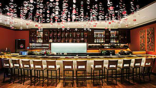Contemporary bar with glass and red bubble decorations hanging from the ceiling
