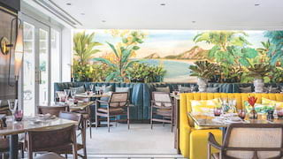 Brightly coloured bistro with black and white mosaic floor and a Rio wall mural