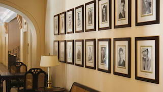 Rows of sepia portrait photos in black frames on a corridor wall