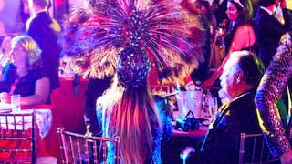 Guests sitting at circular party tables dressed in glamorous carnival outfits