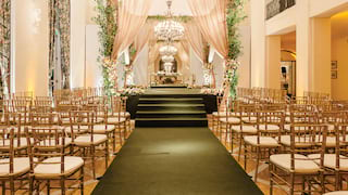 Double-height room set for a wedding ceremony with a central floral pergola