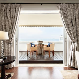 Hotel suite with polished wooden floors looking out to elegant balcony seating