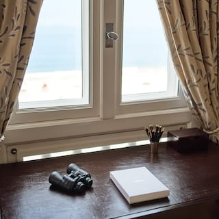 Binoculars and pencil pot on a brown leather topped hotel room desk