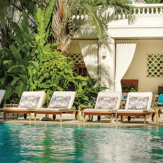 Sunbeds with palm print cushions lining a glittering outdoor pool