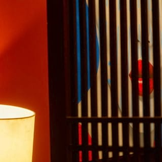 Abstract photo of a portrait of an asian lady next to a table lamp
