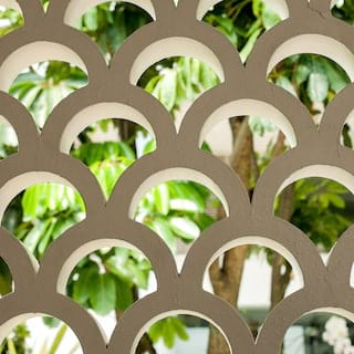 Art deco garden wall with scallop details and lush foliage beyond