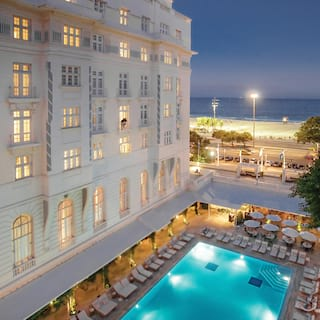 Glamorous lamp-lit outdoor pool in evening light next to a white hotel facade