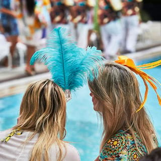 Two ladies wearing brightly coloured feather caps by a poolside
