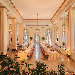 Art deco ballroom with two long banquet tables set for a wedding