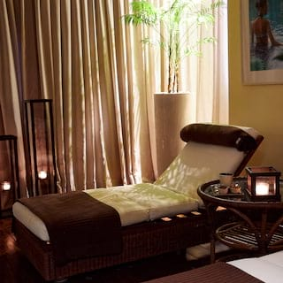Spa therapy bed in a candlelit room with yellow and tan accents