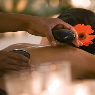 Guest with an orange flower in her hair receiving a hot stone massage