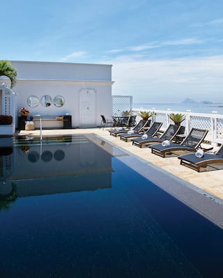 Penthouse balcony pool surrounded by sleek black sunbeds overlooking a beach