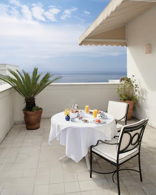 Linen-coated circular table laden with breakfast dishes on a balcony