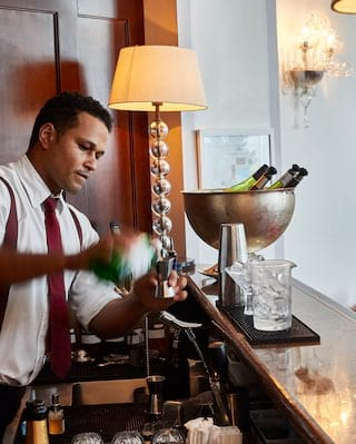 Barman pouring liquor into a cocktail shaker in an elegant lamp-lit bar