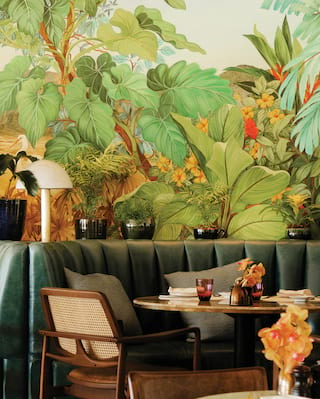 Circular dining tables with green leather seating in front of a Rio wall mural