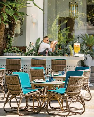Exterior restaurant terrace with blue bamboo chairs surrounded by palm gardens