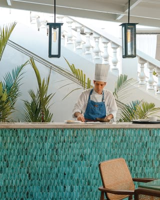 Chef at a blue-tiled restaurant counter backed with potted palm plants