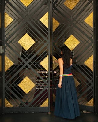 Lady in a dark navy sundress walking through black and gold glass doors