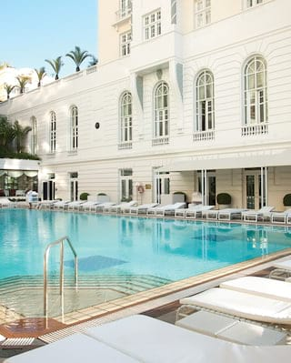 Outdoor restaurant pool surrounded by sunbeds in front of a white hotel facade