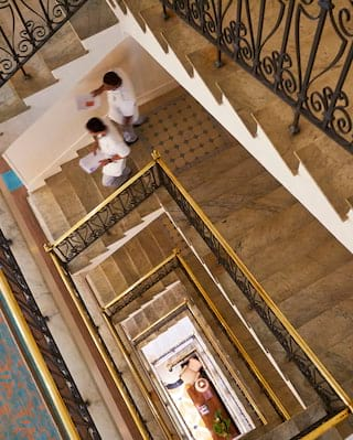 Birds-eye-view of staff descending a stairwell with ornate ironwork railings