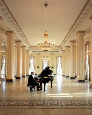 Pianist playing a piano in an empty grand ballroom with a mosaic floor