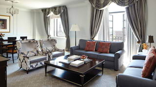 Grand hotel suite lounge with grey accents and large balcony windows