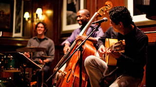 Guitarist, cellist and drummer smiling in the Charleston Grill