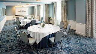 Circular banquet tables set for a meeting in a powder-blue room