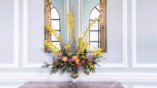 Close-up of a floral display on a granite-topped side table under a gold mirror