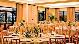 Circular banquet tables surrounded by bamboo chairs in a peach-coloured room