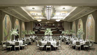 Luxurious ballroom venue with wall murals and circular tables