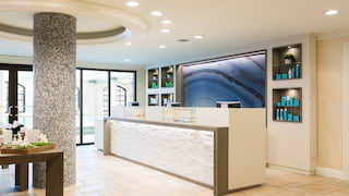 Light and airy spa reception area with large white reception desk