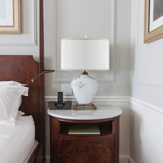 Close-up of an elegant lamp on a marble-topped bedside table