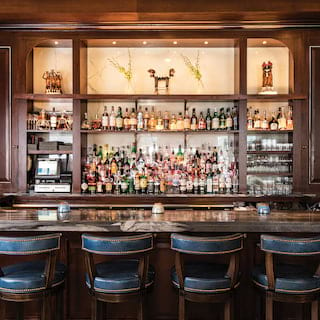 Wood-paneled bar with a marble bar counter and leather bar stools