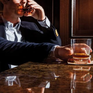 Man resting a whisky glass on a marble bar top