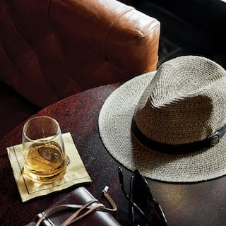 Hat and sunglasses placed next to whisky in a glass
