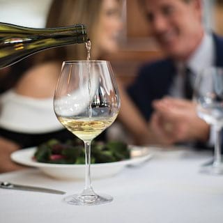 Close-up of white wine being poured from a bottle into a glass