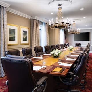 Polished wood boardroom table surrounded by plush black leather chairs