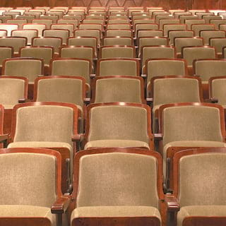 Close-up of vintage-style theater seats in rows rising into the background