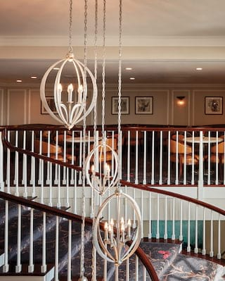 Lobby balcony with a grand staircase and modern chandelier lights