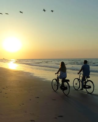 Couple cycling along a shoreline at sunset