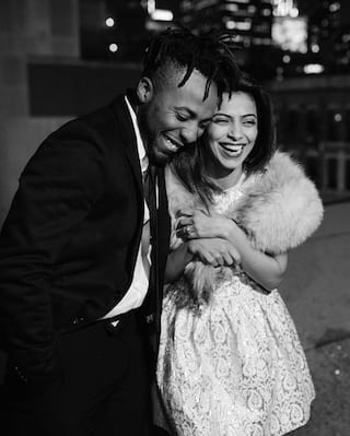 Black and white photo of a couple giggling in formal dress