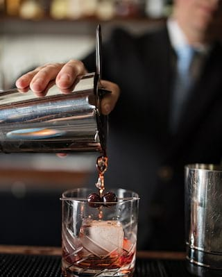 A red cocktail being poured over ice from a shaker